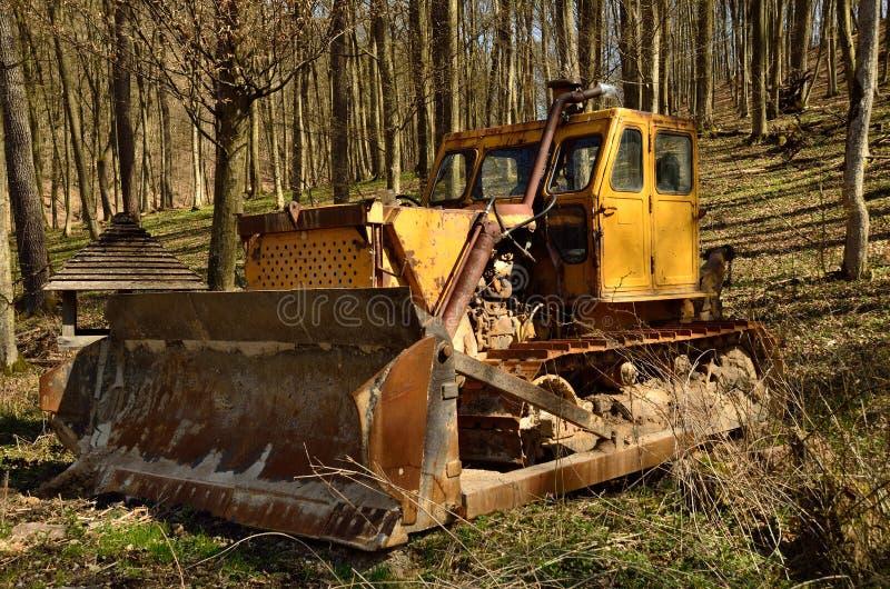 老推土机在森林里 免版税库存照片