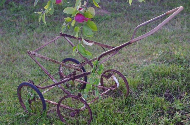 老摇篮车的框架在苹果树下 库存图片