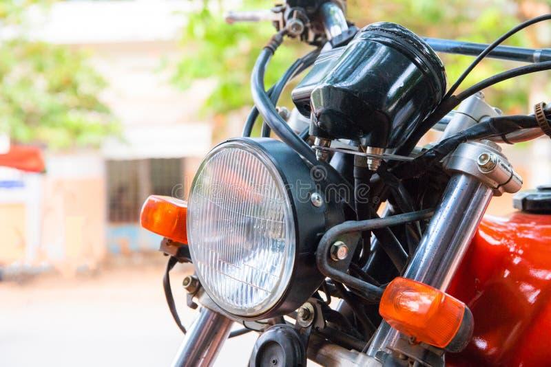 老摩托车车灯  葡萄酒摩托车特写镜头 减速火箭的车红色和白光  库存照片