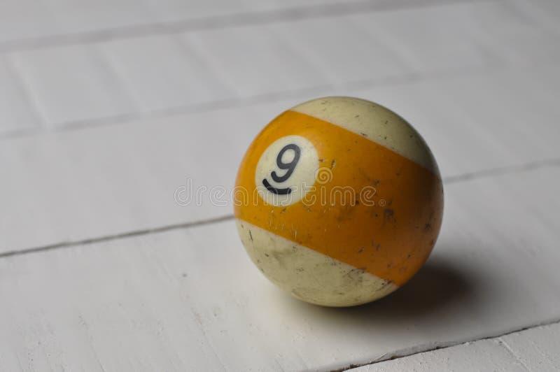 老撞球第9镶边了白色和黄色在白色木桌背景,拷贝空间 免版税库存图片