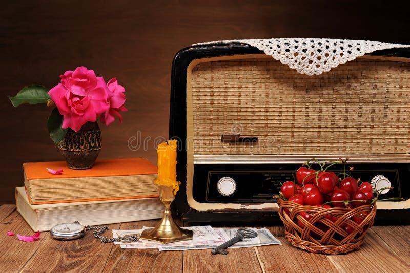 老收音机、花、书和甜樱桃 免版税库存照片