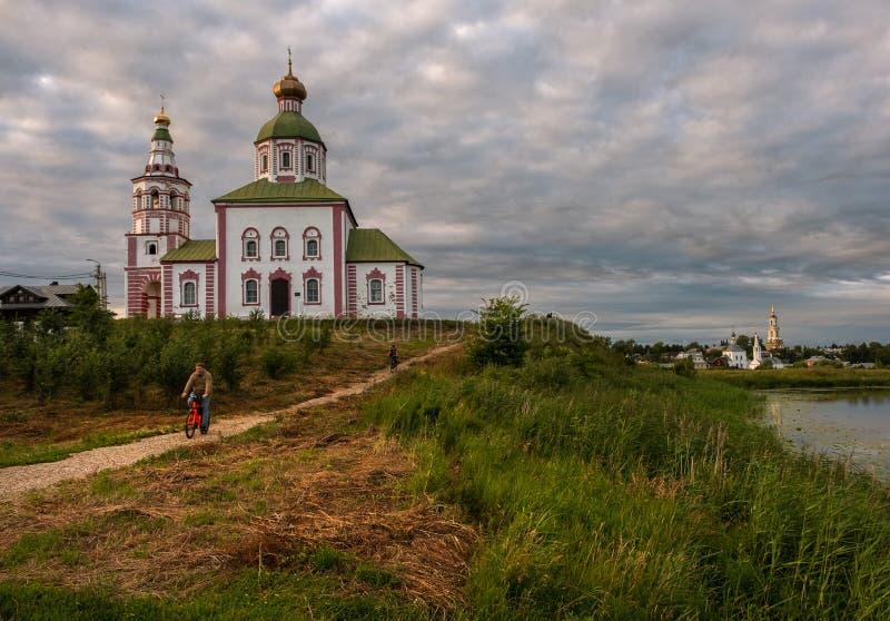 老教会在苏兹达尔日落的 在河的桥梁,荷花 俄国省的秀丽 俄罗斯在 免版税库存图片