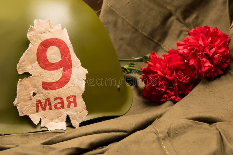 老日历第9页可以,关于一件军事盔甲和两支红色康乃馨在雨衣帐篷背景  图库摄影