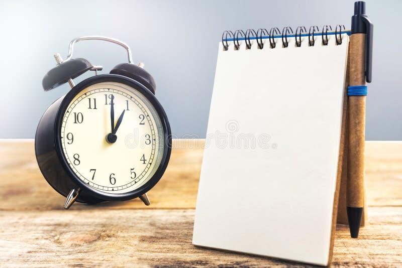 黑老时钟和白纸与笔,在木桌上 免版税图库摄影
