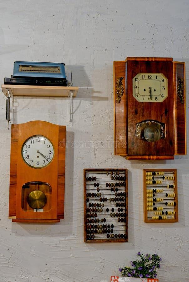 老时钟,垂悬在白色墙壁上的算盘 免版税库存照片