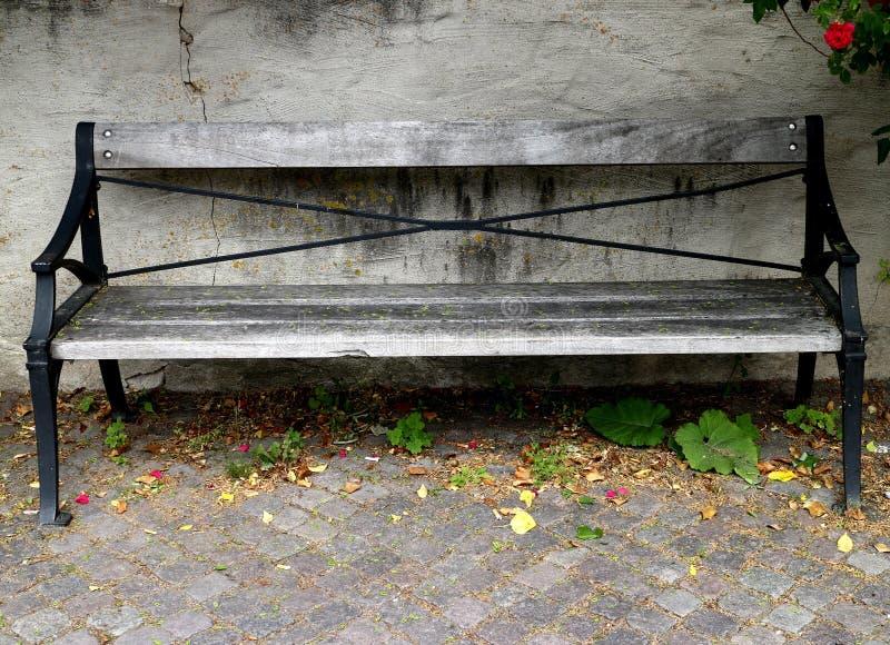 老木公园长椅在一个被风化的石墙前面站立 免版税库存照片
