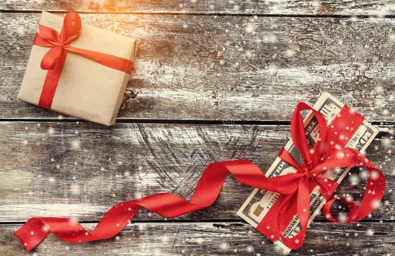 老木头、金钱装饰与红色松驰和礼物圣诞节背景  顶视图 光和雪花的作用 免版税库存图片