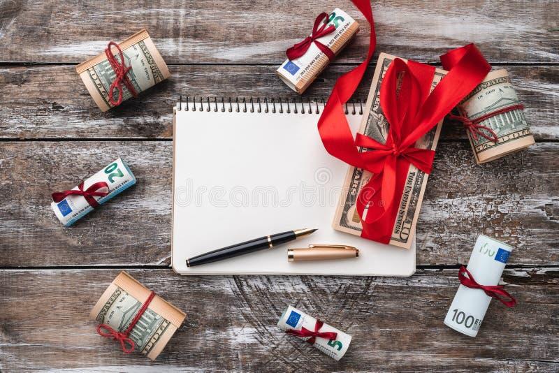 老木头Xmas背景  礼物在美国和欧洲金钱 礼品节假日意大利罗马纪念品 顶视图 在笔记本的文本空间 库存照片