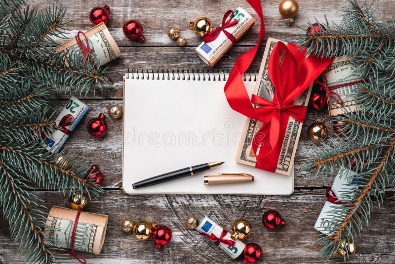 老木头Xmas背景  礼物在美国和欧洲金钱 红色和黄色中看不中用的物品 免版税库存照片
