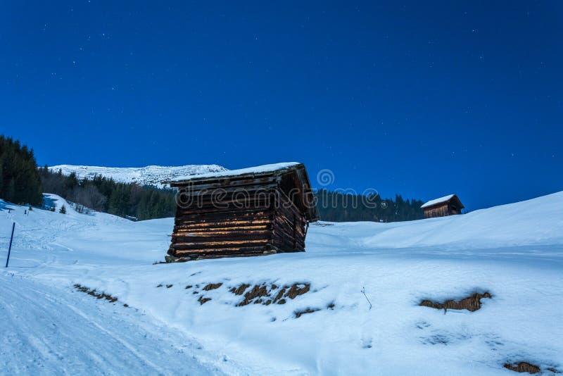 老木小屋和多雪的山在滑雪胜地Serfaus Fi 免版税图库摄影