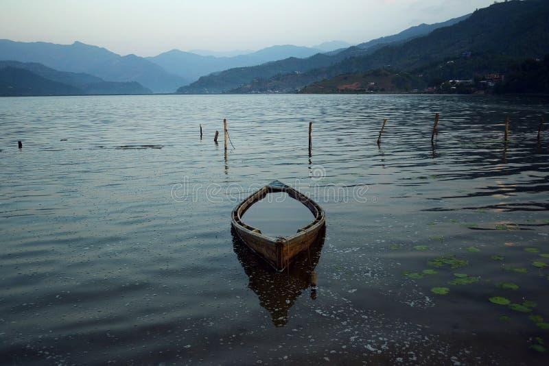 老木小船在湖的水中反射了 库存图片