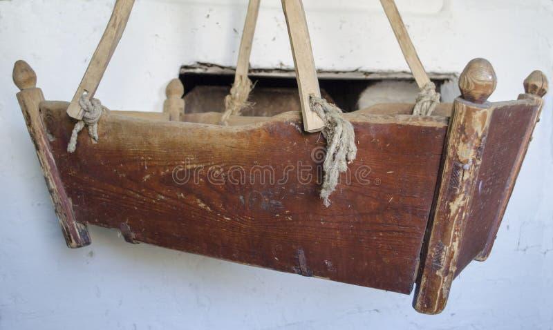 老木摇篮在村庄房子里 图库摄影