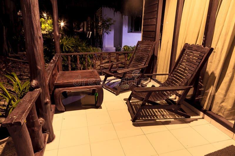老木桌和木椅子,在平房房子的门廊的立场 在街道上在晚上 免版税库存图片