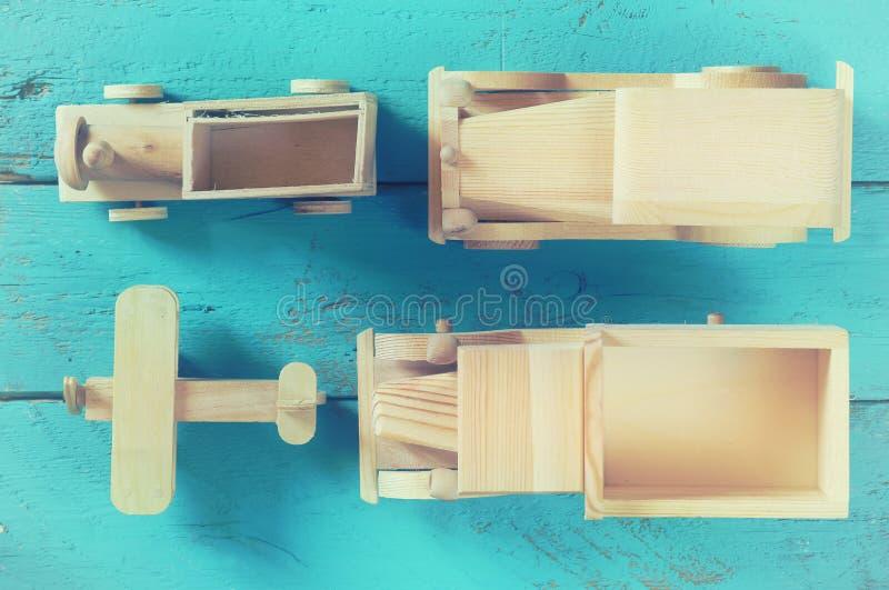老木运输玩具:火车、汽车、轨道和飞机在蓝色木背景 被过滤和被定调子的葡萄酒 免版税库存图片
