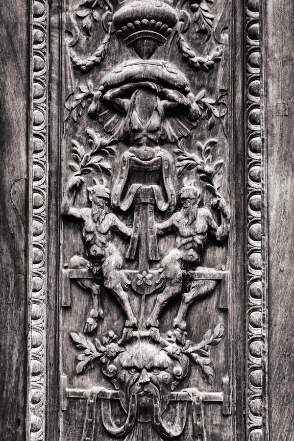 老木门刻记与恶魔般的图 库存照片
