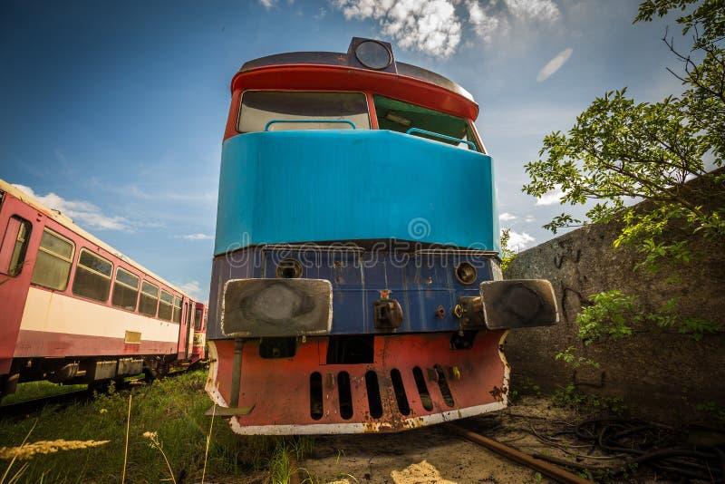 老机车在有绿草的火车公墓和树在背景和伟大的多云天空中 免版税库存图片