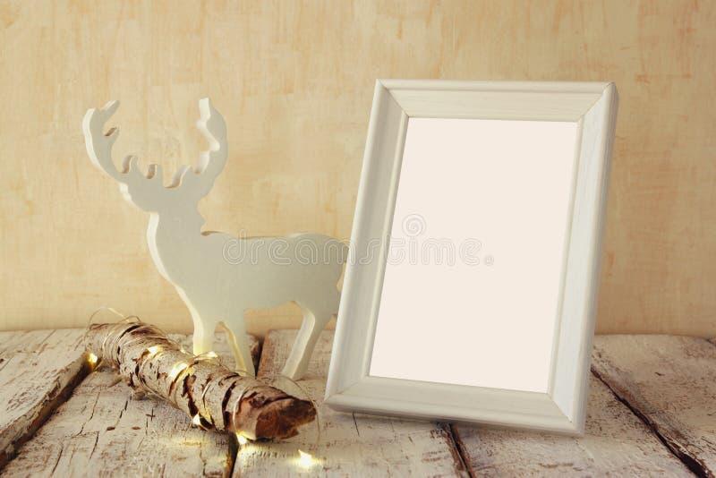 老树日志的高关键图象与神仙的圣诞灯、驯鹿和空白的照片框架的在木桌上 选择聚焦 免版税库存照片