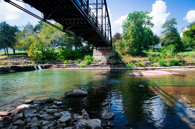 老桥梁在下面河投下在岩石的五颜六色的阴影 图库摄影