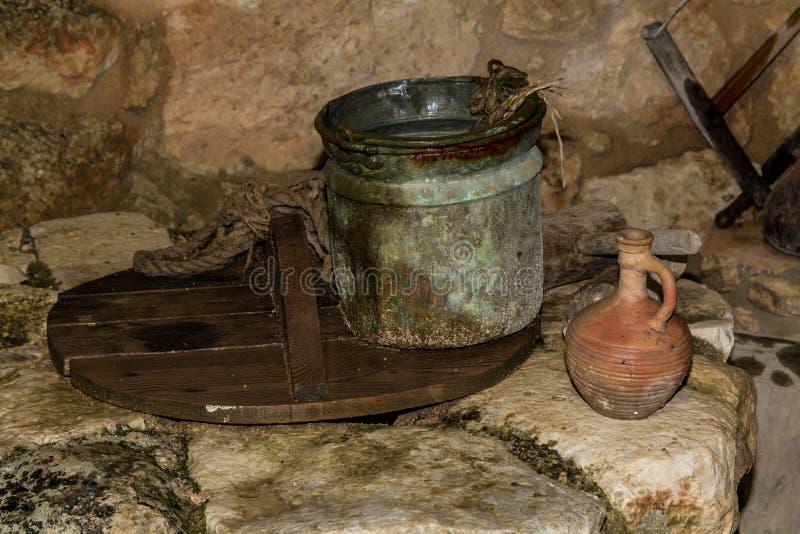 老桶和黏土水罐在水井在拿撒勒村庄,以色列 库存照片