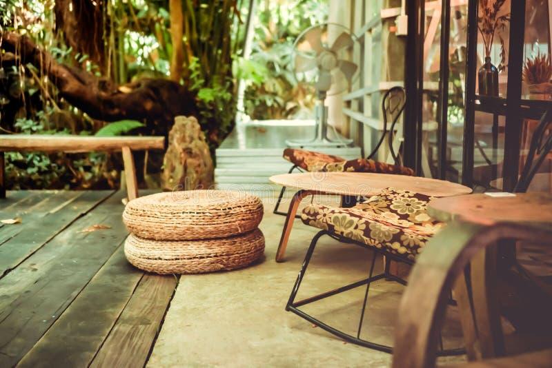 老椅子葡萄酒减速火箭的样式在阳台moden有自然的房子为放松并且变冷  图库摄影