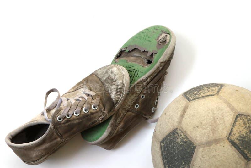 老橄榄球和老鞋子在白色背景 免版税图库摄影