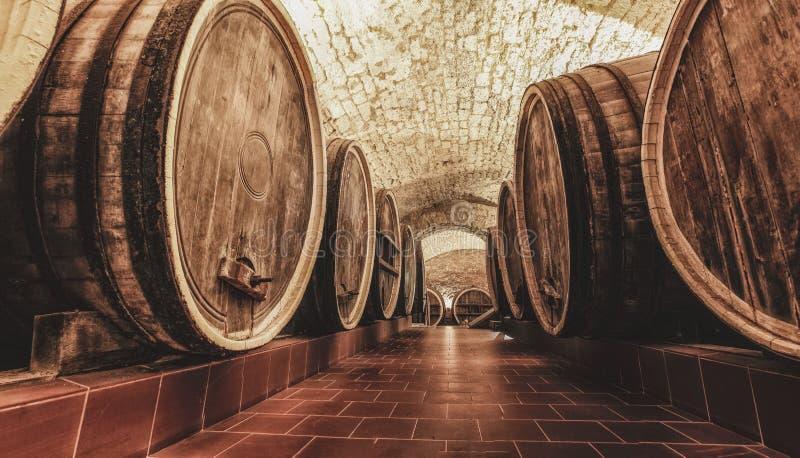 老橡木桶在古老葡萄酒库里 库存图片