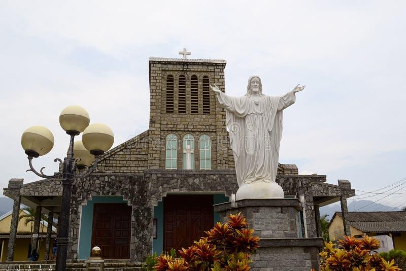 老殖民地天主教会和白色耶稣基督雕象 免版税库存照片