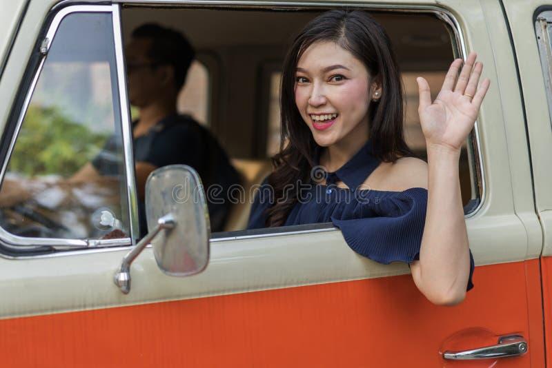 老汽车和举她的手愉快的妇女葡萄酒窗口  库存照片
