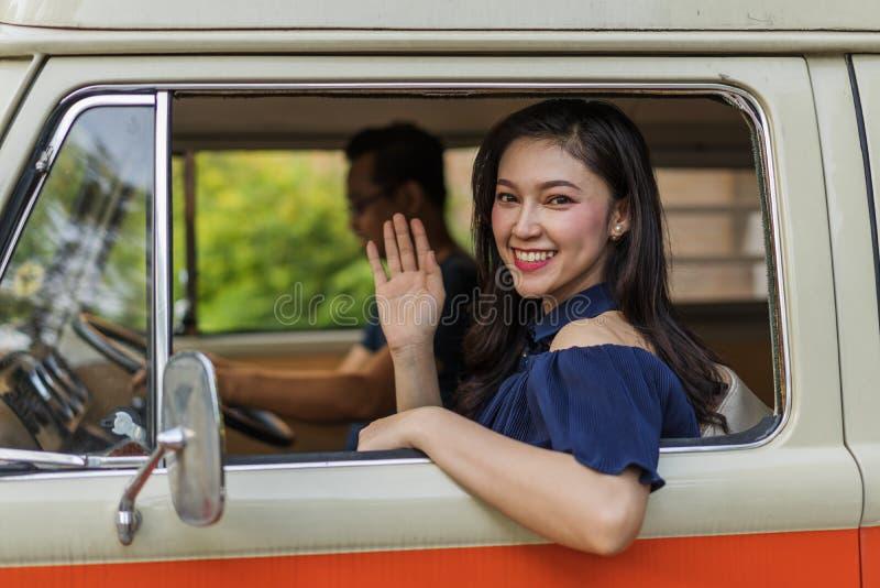 老汽车和举她的手愉快的妇女葡萄酒窗口  免版税库存照片