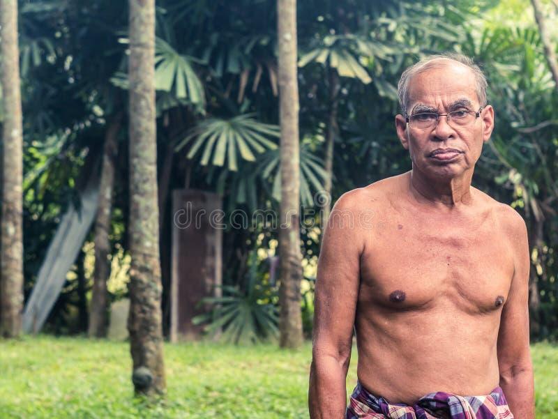 老泰国花匠人在橡胶庭院里 图库摄影