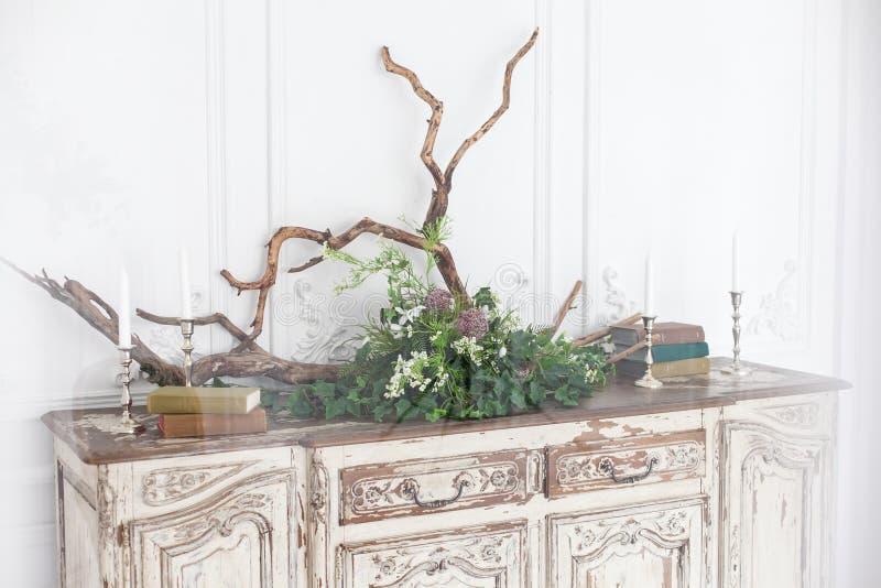 老洛可可式的五斗橱用书、蜡烛、漂流木头和植物装饰对墙壁有灰泥的 免版税图库摄影