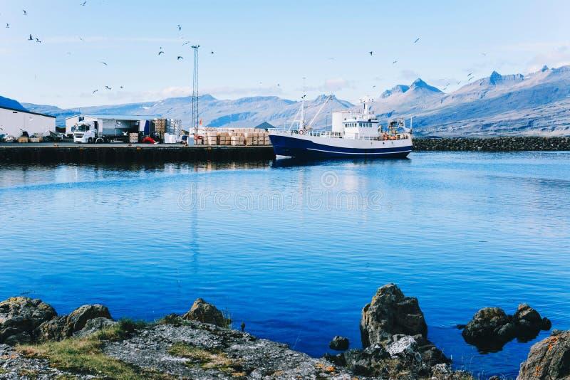 老渔夫小船近的渔村在冰岛 库存照片