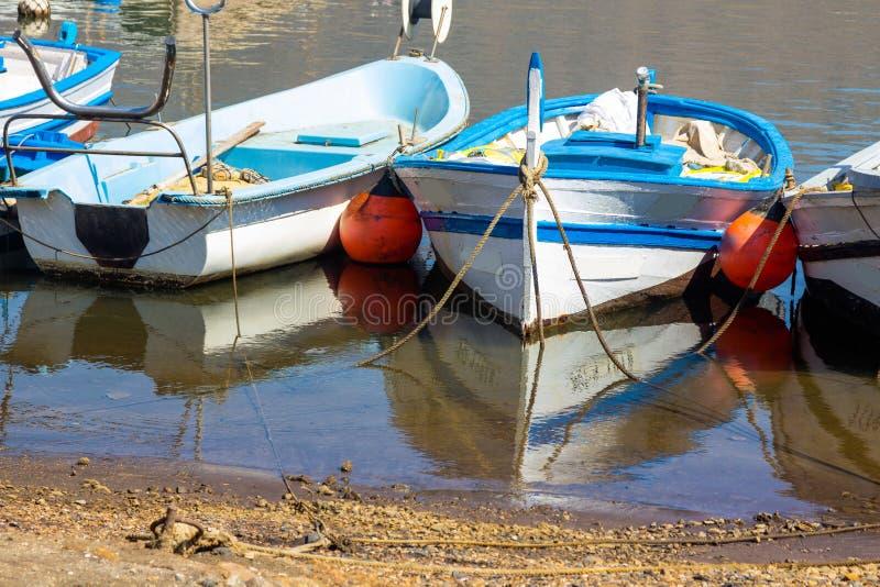 老渔船被栓对与风平浪静和反射的岸 免版税库存图片