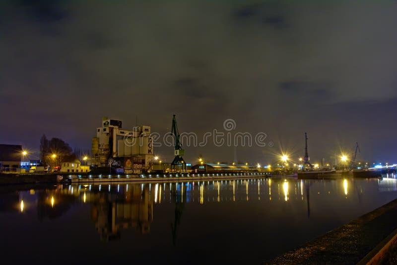 老港口在跟特,有工业筒仓` s和起重机的,在晚上 免版税图库摄影