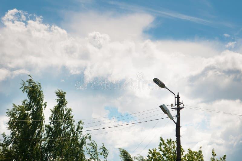 老灯岗位、树叶子和蓝天与云彩 日 免版税库存照片