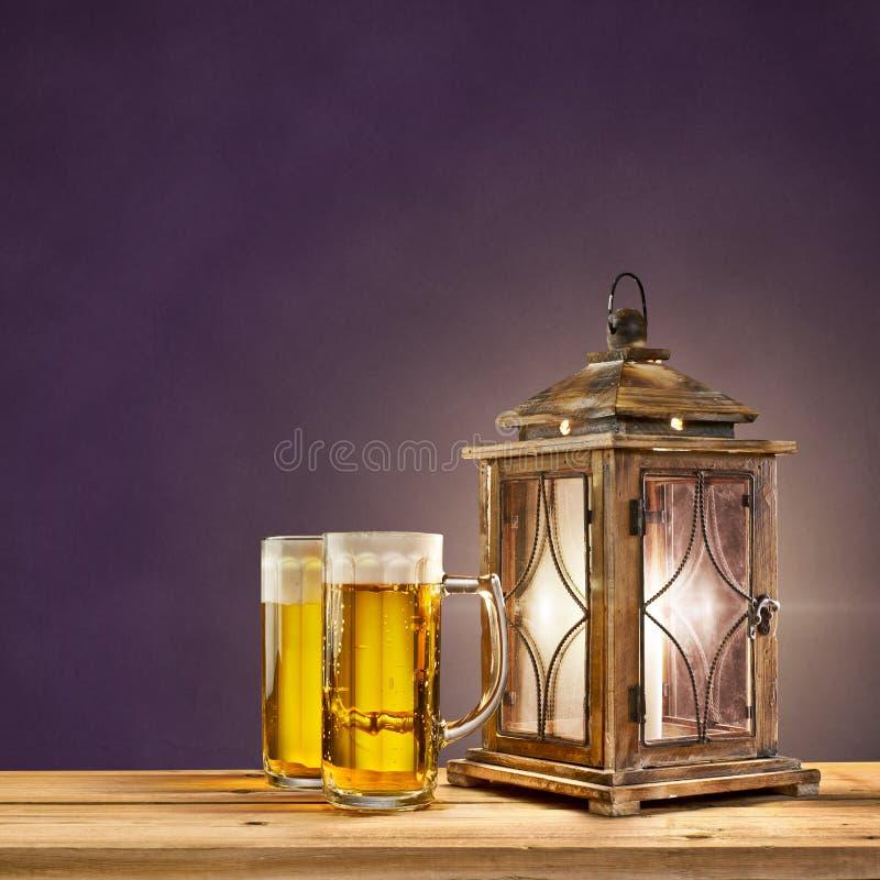 老灯笼用在紫色葡萄酒背景的啤酒 免版税库存照片