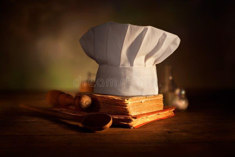 老烹饪书、厨师帽子和木匙子 在老木桌上的厨房辅助部件 免版税图库摄影