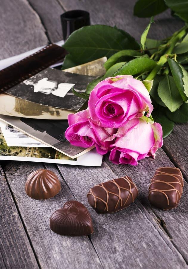 老照片变粉红色玫瑰和巧克力在黑暗的木背景 库存图片