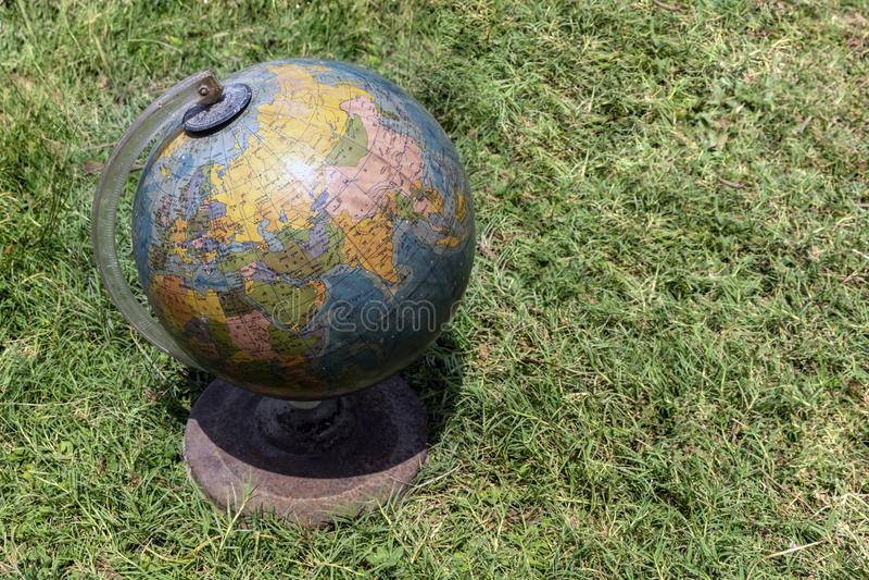 老牌孟加拉人语言写的世界地球-在草的古色古香的世界地球归档了背景 显示印度 免版税库存照片