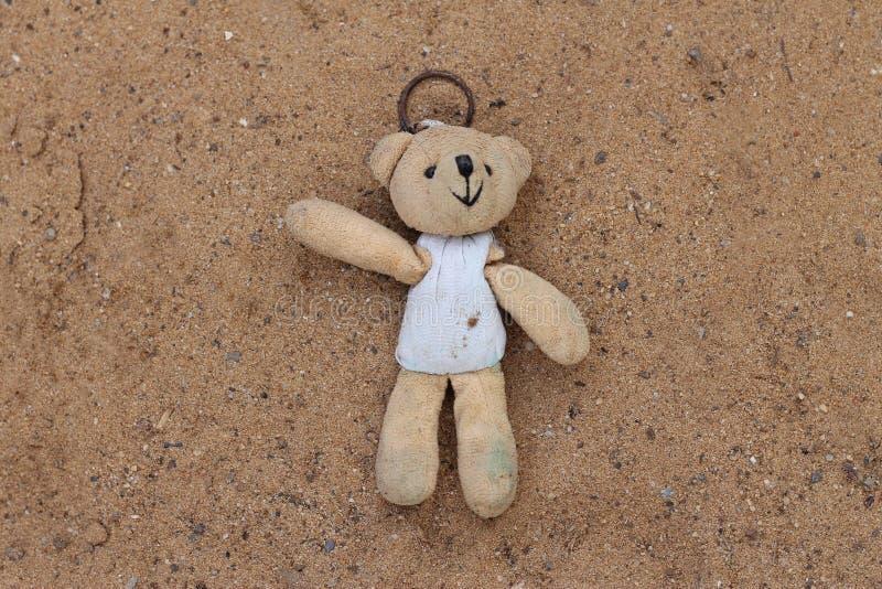 老玩具熊在沙子,没人感兴趣的玩具单独被留下 库存图片