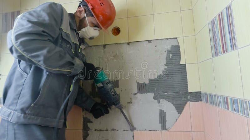 老瓦片的爆破有手提凿岩机的 老墙壁的整修在卫生间或厨房里 免版税库存图片