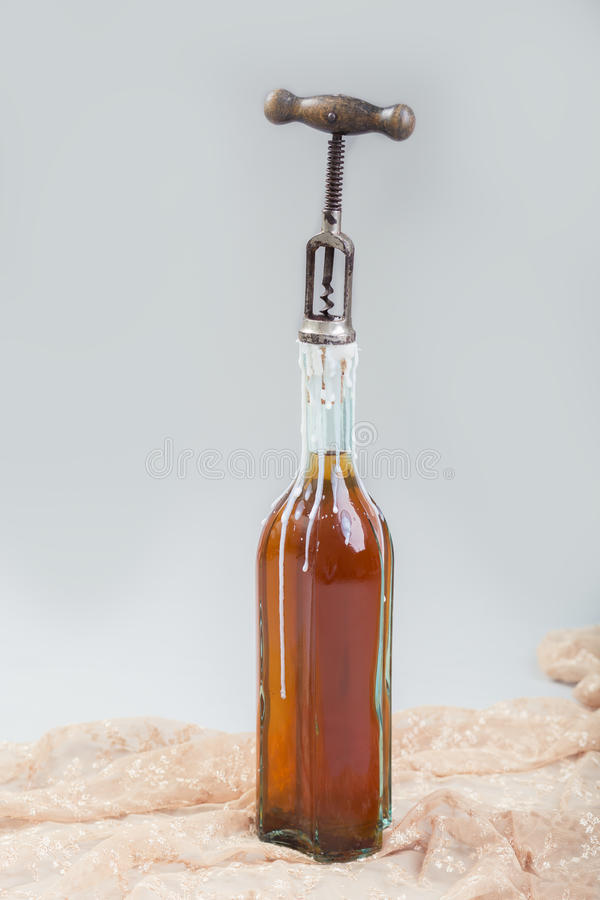 老瓶与拔塞螺旋的酒 免版税库存图片