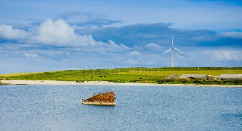 老生锈的凹下去的小船和eolic爱好者在背景中 免版税图库摄影