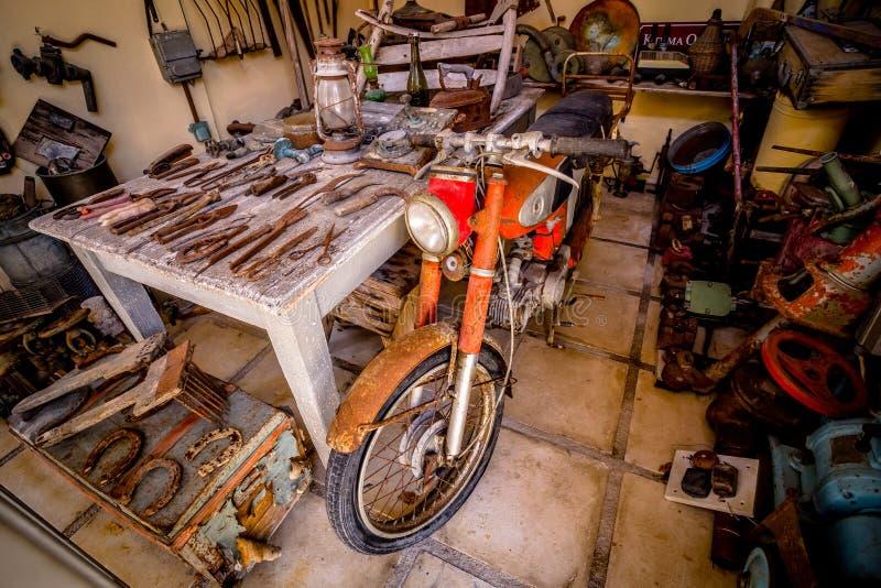 老生锈的摩托车在有老生锈的工具的棚子 免版税库存图片