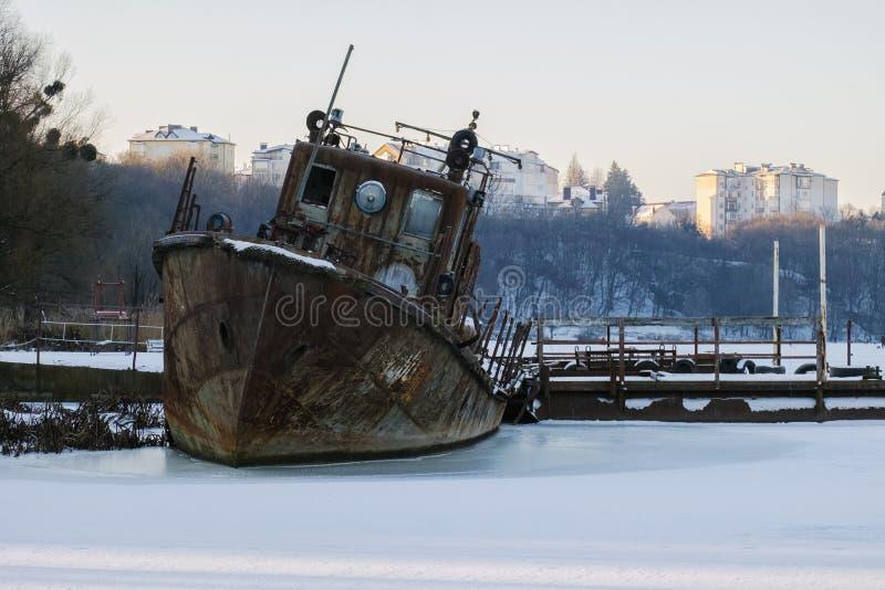老生锈的救助艇在冰结冰了 免版税库存照片