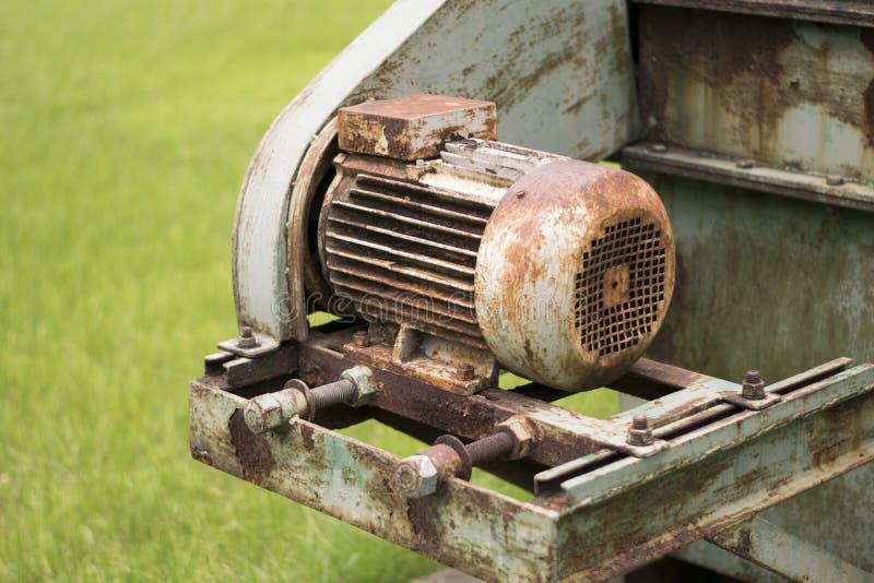 老生锈的机器在绿草背景中 免版税库存图片