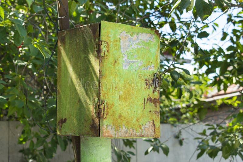 老生锈的绿色削皮金属邮政箱子(接线盒)在Th下 免版税库存图片