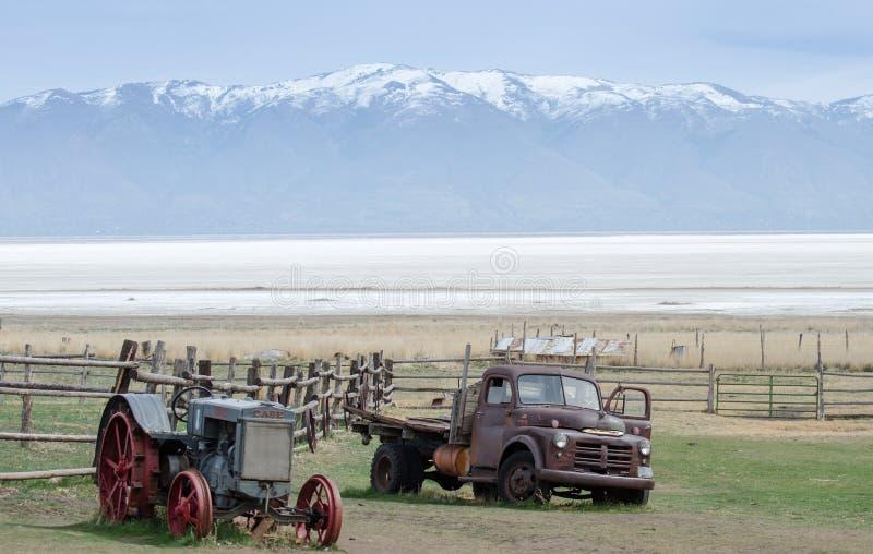 老生锈的被放弃的拖拉机 并且在积雪覆盖的Wasatch山frot的卡车  从羚羊海岛的看法 美国犹他 免版税库存图片