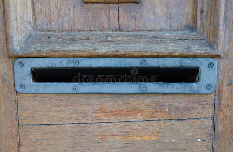 老生锈的金属打开了在木门的邮箱没有信件里面 免版税库存图片