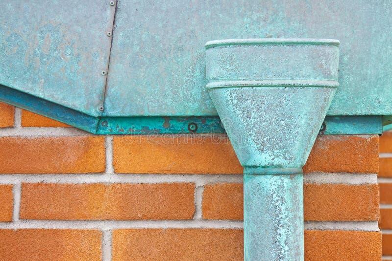 老生锈的铜落水管对砖墙-与拷贝空间的图象 免版税库存图片